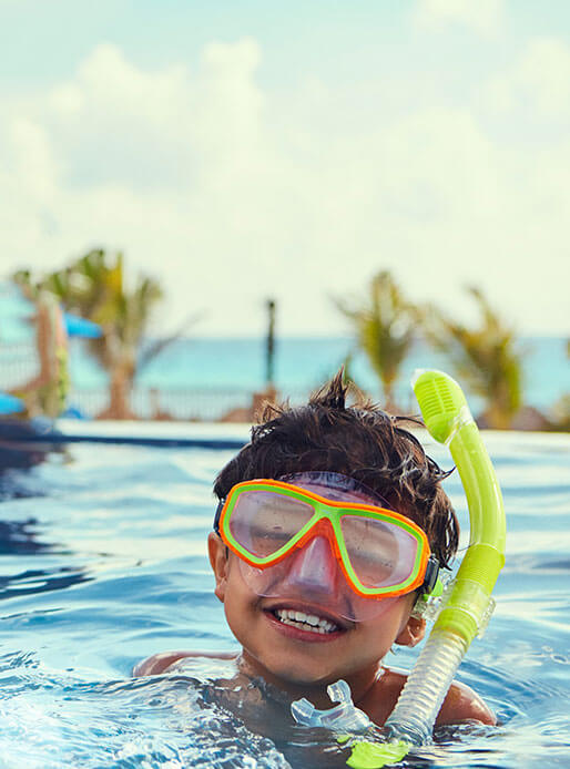 happy boy smiling in pool with snorkel and goggles by the beach