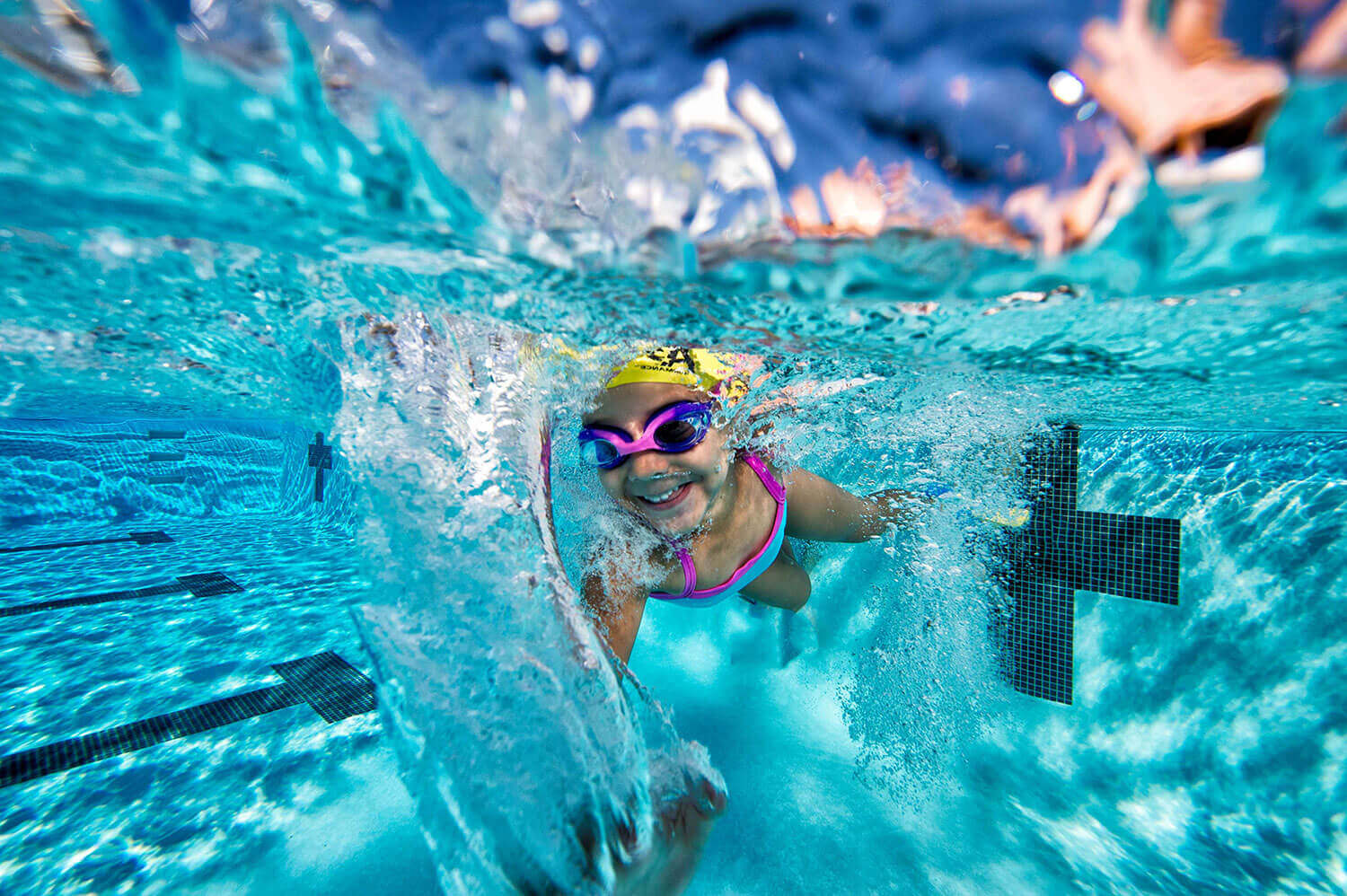 happy smiling child with goggles swim cap and swim gear in pool underwater with lots of bubbles