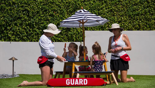 sun fun lifeguard supervisors having a pool party with kids outside by the pool