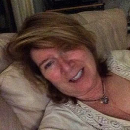 woman relaxing on couch in living room smiling selfie testimonial